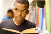 Male african american college student reading in library — Stock Photo