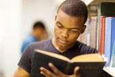 Male african university student reading in library — Zdjęcie stockowe