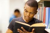 Mannelijke afrikaanse universiteitsstudent lezen in bibliotheek — Stockfoto
