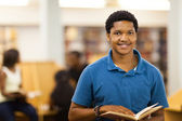 Male african american college student reading book in library — Stock Photo