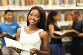 Beautiful african american college girl in library — Stock Photo