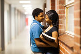 African american college boyfriend hugging girlfriend in college passage — Stock Photo