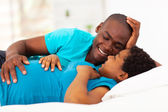 Expecting african american couple lying on bed and chatting — Stock Photo