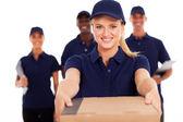 Friendly young delivery woman presenting parcel with colleagues — Stock Photo