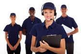 IT service call center operator with headphones and team — Stock Photo