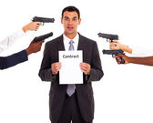 Businessman holding forced contract at gun point — Stock Photo