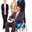 Businessman in wheelchair with colleagues in background — Stock fotografie