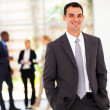 Handsome modern businessman in office with colleagues in background — ストック写真