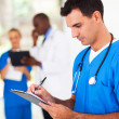 Male medical worker writing report in hospital - Stock Photo