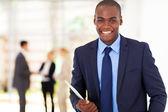 Gut aussehend afroamerikanischer geschäftsmann mit tablet-pc im büro — Stockfoto