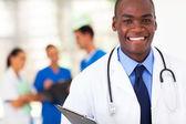 バック グラウンドで同僚とハンサムなアフリカ系アメリカ人医師 — ストック写真