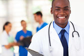 Handsome african american medical doctor with colleagues in background — 图库照片