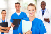 Pretty medical nurse and colleagues in hospital — Stock Photo