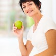 Woman holding a green apple — Stock Photo