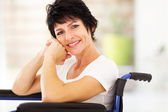 Middle aged woman sitting on wheelchair — Stockfoto