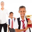 Schoolgirl holding trophy in front of teacher and classmate — Stockfoto #21978827