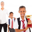 图库照片: Schoolgirl holding trophy in front of teacher and classmate