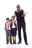 Elementary school teacher and students full length portrait on white — Stock Photo