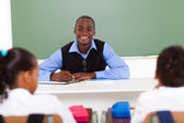 African american elementary school teacher in classroom with students — Stock Photo