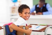 Cute elementary schoolboy looking back in classroom — Stock Photo