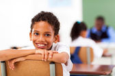 Male primary school student in classroom with classmate and teacher — Stock Photo