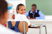 Cute elementary schoolgirl in classroom with classmate and teacher — Stock Photo