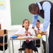 Elementary teacher helping student in classroom — Stock Photo #21980611