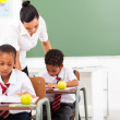 Caring elementary school teacher and students in classroom — Stock Photo #21980755