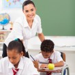 Beautiful elementary school teacher in classroom with students — Stock Photo