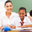 Beautiful primary school teacher and students in classroom — Stock Photo #21981083