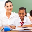 Beautiful primary school teacher and students in classroom — Stock Photo