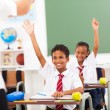 Elementary school students arms up in classroom — Stock Photo