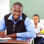 Male teacher preparing lesson in classroom — Stock Photo #21985219