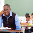 Handsome african school teacher in classroom — Stockfoto