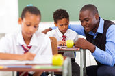 Elementary school teacher helping student in classroom — Stock Photo