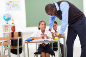 Elementary teacher helping student in classroom — Stock Photo
