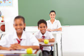 Pretty female school teacher in classroom with students — Stok fotoğraf