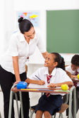 Friendly female elementary school teacher talking to student in classroom — Stock Photo