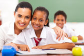 Pretty elementary school educator and students in classroom — Stock Photo