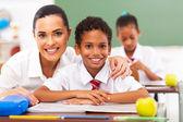 Attractive elementary school teacher and students in classroom — Fotografia Stock