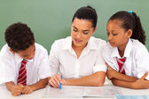 Pretty elementary school teacher helping students in classroom — Stock Photo