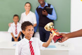 School boy receiving a trophy in classroom — Stock Photo
