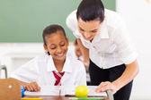 Elementary school teacher helping student — Stock Photo