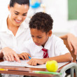 Caring elementary school teacher helping student in classroom - Stock Photo