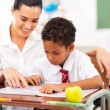 Caring elementary school teacher helping student in classroom — Stock Photo