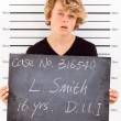 Teen boy get arrested for drunk driving and taking police mug shot - Stock Photo
