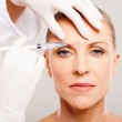Cosmetic surgeon giving face lifting injection — Stock Photo