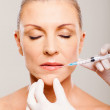 Mature woman receiving lips injection — Stock Photo #22389419