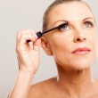 Senior woman putting mascara — Stock Photo #22389943