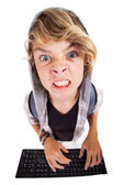 Overhead view of angry teen boy playing on computer keyboard — Stock Photo